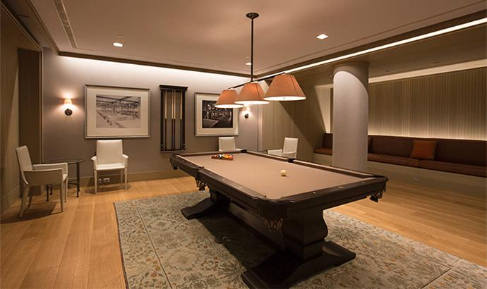 A rich, dark wooden pool table with tan felt in a contemporary recreation room at Crystal Green apartments in NYC.