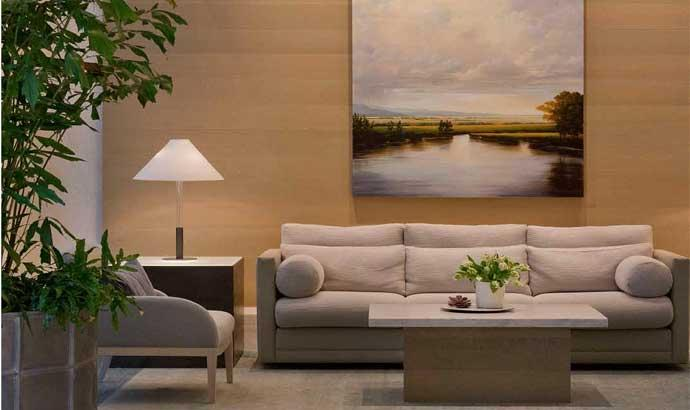 A contemporary living room set with a beige couch and sitting chair in a warmly lit lobby of Crystal Green in NYC.