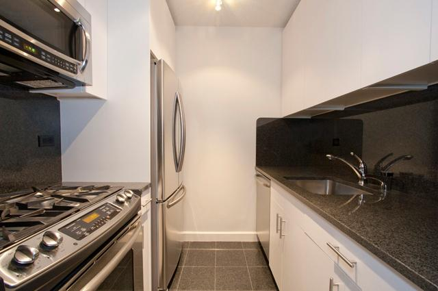 View of a small kitchen with updated stainless steel appliances, white walls, and white cabinets in New York City.