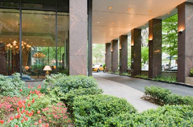 View of the front driveway of a luxury New York City apartment building with manicured landscaping in the foreground.