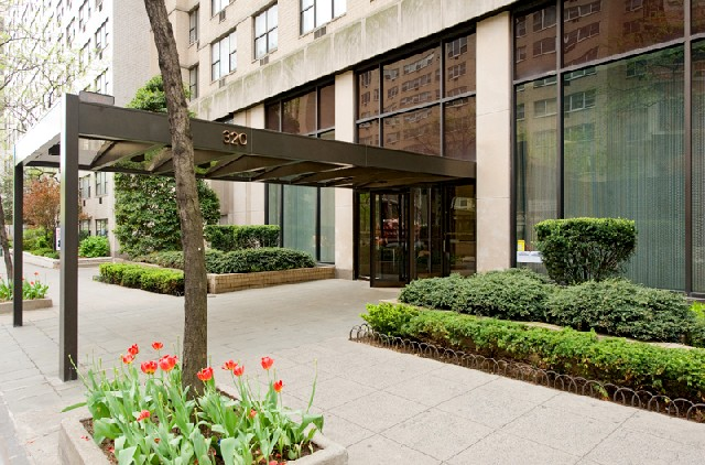 Front entrance of the Belmont luxury apartments in New York City with green plants and red tulips.
