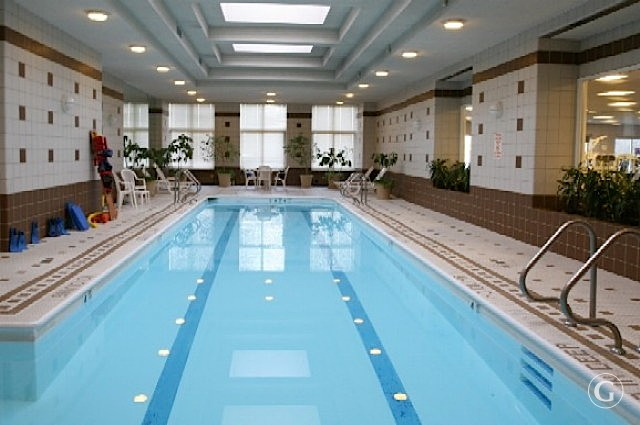 An indoor swimming pool with lanes surrounded by white and tan tile at the Brittany apartments in New York City.