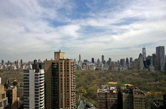 Skyline view of New York City with apartment buildings in the foreground on a partly cloudy day.