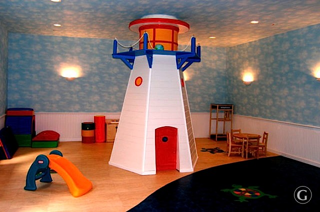 A children's play room with plastic lighthouse and wooden chairs in the background.