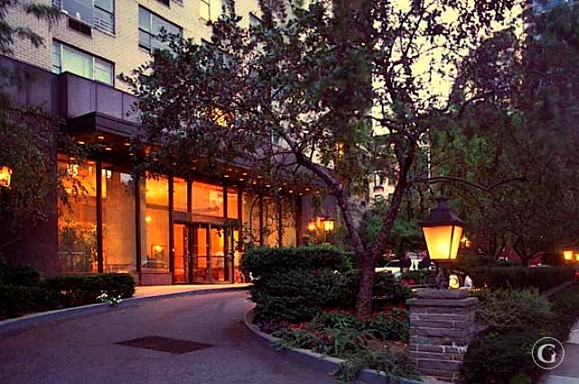 View of the front driveway at the Andover luxury apartments in New York City at dusk with golden lights.