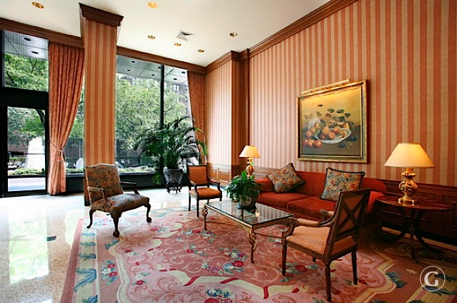 A couch and set of three chairs on an antique rug in a sitting area of the Andover apartments front lobby.
