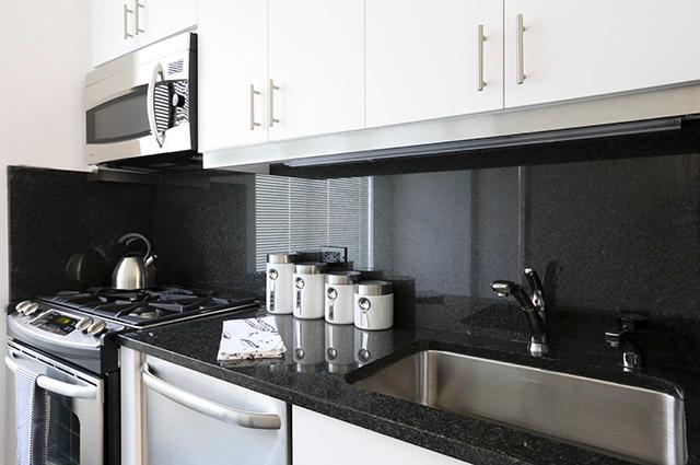 An updated kitchen with black countertops and backsplash with white cabinetry in a New York City apartment.