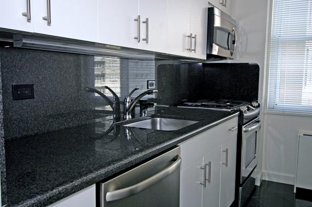Black countertops along white cabinetry and stainless steel appliances in a luxury New York City apartment.