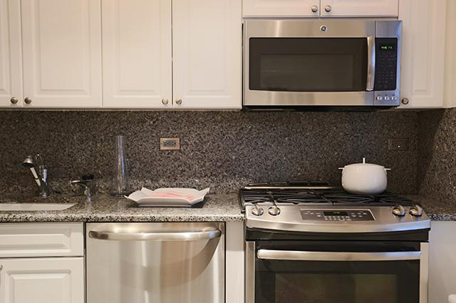 An updated luxury kitchen with white cabinets and stainless steel appliances with a white pot on the stove.