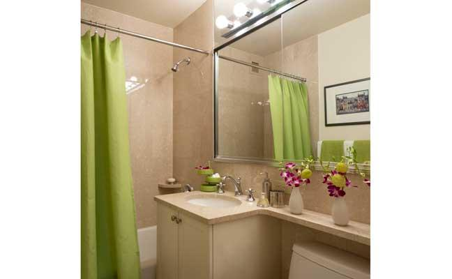 A tan bathroom with single vanity and lime green shower curtain in a New York City apartment.