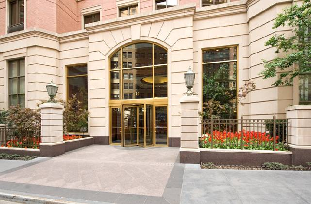 Front entrance of Liberty Plaza with golden doors and blooming red tulips near the sidewalk.