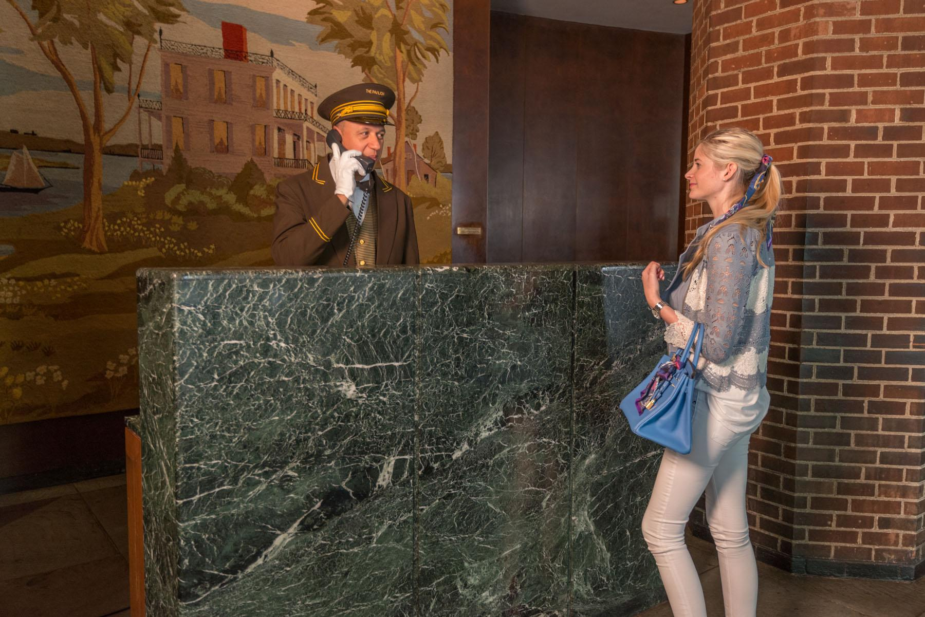 A blonde woman stands at the front desk where a doorman speaks on the phone.